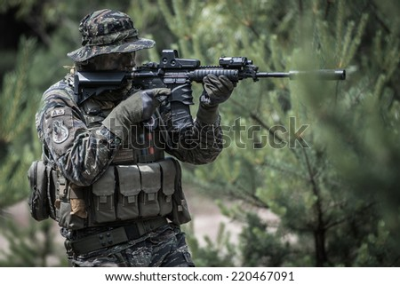 US soldier aiming with assault rifle at target - stock photo