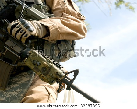 US soldier in camouflage uniform holding his rifle - stock photo