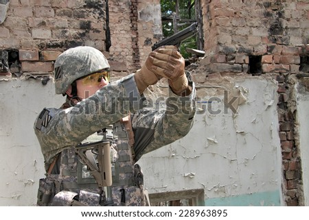 US Soldier on urban patrol mission aiming his pistol