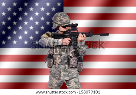 US soldier with his assault rifle on flag background - stock photo