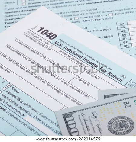 US Tax Form and dollars - studio shot - stock photo