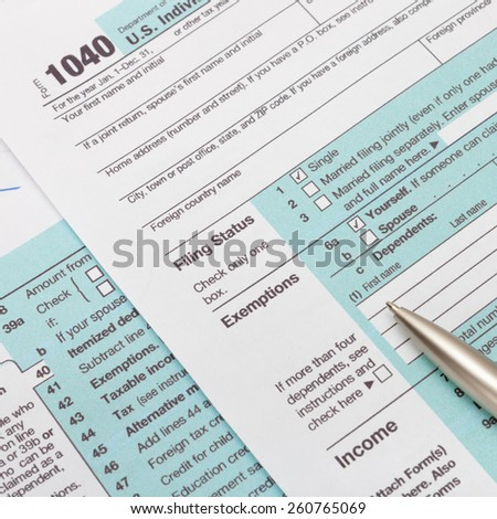 US 1040 Tax Form and silver ball pen - studio shot - stock photo