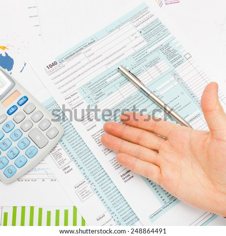 US 1040 Tax Form, calculator, male hand and silver pen - studio shot