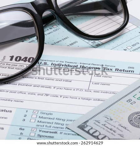 US 1040 Tax Form, glasses and dollars - studio shot - stock photo