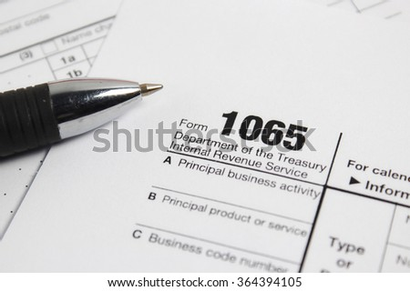 US 1065  tax form with a pen selective focus / taxation concept