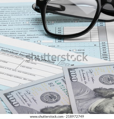 US Tax Form 1040 with calculator and 100 dollars - 1 to 1 ratio - stock photo