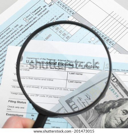 US Tax Form 1040 with magnifying glass - 1 to 1 ratio - stock photo