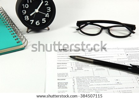 US tax form 1040 with pen and alarm clock on white table  / taxation concept/selective focus - stock photo