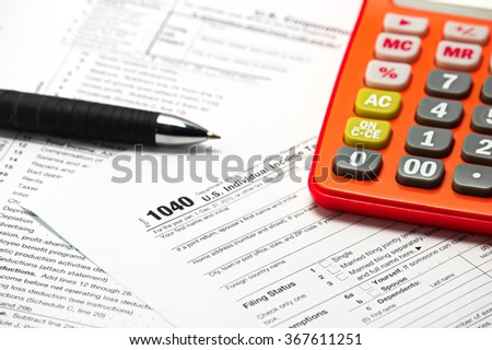 US tax form with pen and calculator selective focus / taxation concept - stock photo