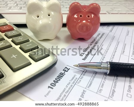 US tax form 1040 with pen, calculator and pig.