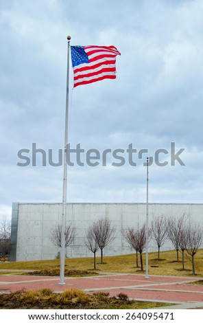 US United States Flag handing proudly over the the Liberty State Park 9/11 Memorial in New Jersey - stock photo