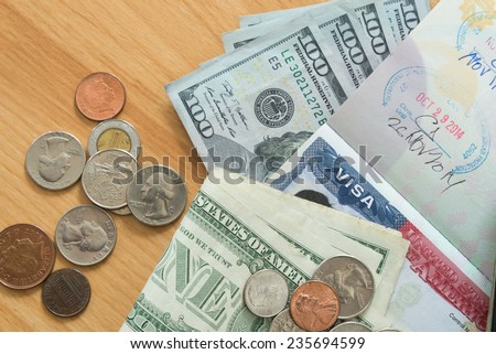 US Visa on passport with dollar bills coins - stock photo