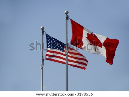 usa and canadian flags on blue sky