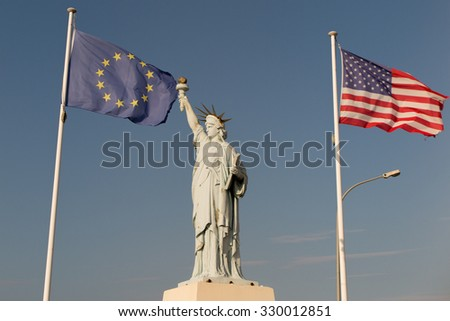 USA and European Union flags, Alliance.  Statue of Liberty, Blue sky background. - stock photo