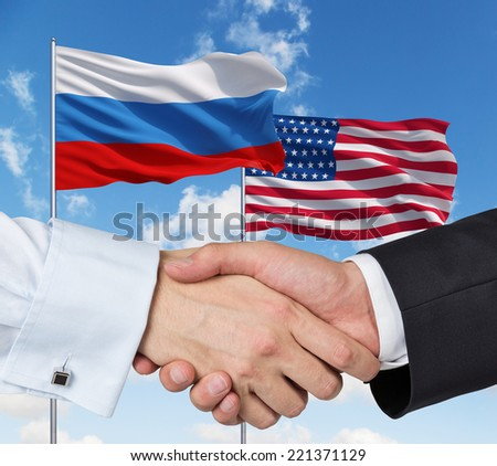 USA and Russian handshake on a blue sky background. - stock photo