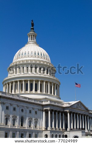 USA Capital dome with the flag waving against a blue sky background. - stock photo