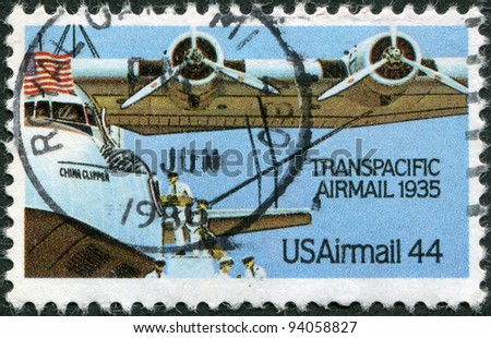 """USA - CIRCA 1985: A stamp printed in the USA, dedicated to 50th anniversary of the trans-Pacific mail flights, shows the loading of the aircraft-mail Martin M-130 """"China Clipper"""", circa 1985 - stock photo"""