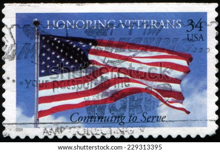 USA - CIRCA 2001: A stamp printed in United States shows American flag on the background of blue sky. Honoring veterans. Continuing to serve, circa 2001 - stock photo