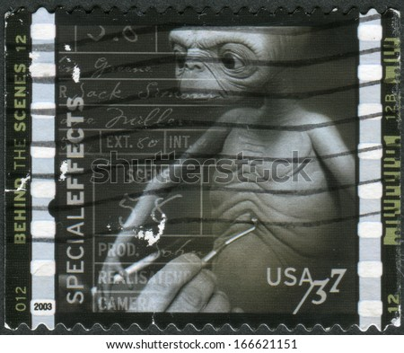 USA - CIRCA 2003: Postage stamp printed in the USA, American Filmmaking: Behind the Scenes, Special effects (Mark Siegel working on model for E.T. The Extra-Terrestrial), circa 2003 - stock photo