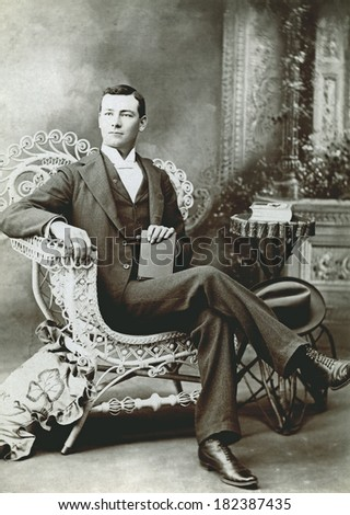 USA - COLORADO - CIRCA 1895 A vintage cabinet card photo of a gentleman holding a fedora hat. He is sitting in a chair while holding a book. Photo from the Victorian era. CIRCA 1895 - stock photo