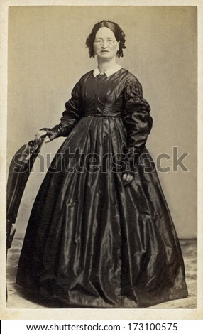 USA - CONNECTICUT - CIRCA 1861 - A vintage Cartes de visite photo of an pioneer woman standing with hand on chair and is dressed in hoop skirt dress. Photo from the Civil War Victorian era. CIRCA 1861 - stock photo