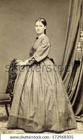 USA - CONNECTICUT - CIRCA 1864 - A vintage Cartes de visite photo of young pioneer woman standing with hand on chair and dressed in hoop skirt dress. Photo from the Civil War Victorian era. CIRCA 1864 - stock photo
