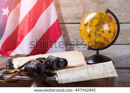 USA flag behind globe. Map and inkwell with feather. Morning in captain's cabin. Voyage along the american coast. - stock photo