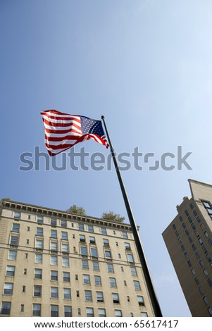 USA flag on blue  sky background with building