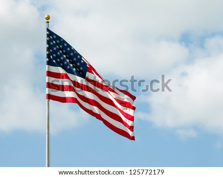 USA flag waving with a cloudy blue sky - stock photo