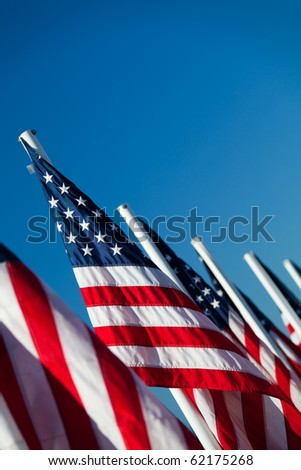 USA flags in a row - American flags lined up, shot angled under clear blue sky - stock photo