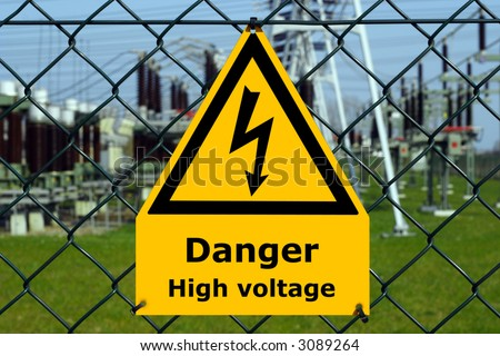 USA high voltage sign with substation, blue sky and green grass in the background.