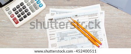 USA IRS tax form 1040 for year 2015 with pencils and calculator with a laptop keyboard on wooden desk. Sized to fit a popular social media cover image placeholder - stock photo