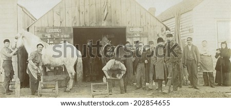USA - KANSAS - CIRCA 1890 A panoramic vintage photo of a blacksmith's shop. There are two workers shoeing two horses. The shop is a wooden building. This photo is from the Victorian era. CIRCA 1890 - stock photo