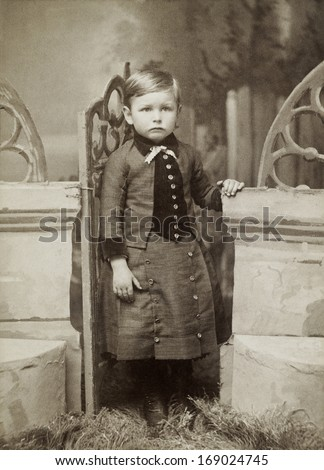 USA - Kansas - CIRCA 1890 - A vintage antique photo of a three year old little boy dressed in Victorian style clothing. He is standing next to a stone. A photo from the Victorian era. CIRCA 1890 - stock photo