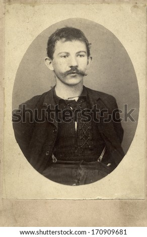USA - KANSAS - CIRCA 1870 A vintage photo of a poor young pioneer man with a mustache. He is wearing a tattered lace up shirt with jacket and suspenders. Photo is from the Victorian era. CIRCA 1870 - stock photo