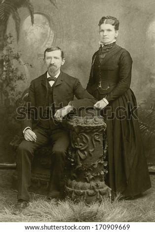 USA - KANSAS - CIRCA 1885 - A vintage photo of a young couple. The husband is sitting and the wife is standing. She is dressed in a Victorian style dress. A photo from the Victorian era. CIRCA 1885 - stock photo