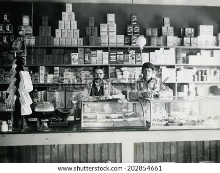 USA - KANSAS - CIRCA 1890 An old vintage photo of an early grocery store stocked with goods. The male store owner and employee are behind the counter. This photo is from the Victorian era. CIRCA 1890 - stock photo