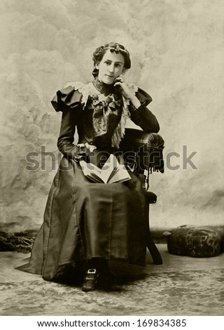 USA - MASSACHUSETTS - CIRCA 1897 - A vintage photo of a young woman. The woman is sitting in a chair. She is dressed in a beautiful Victorian style dress. A photo from the Victorian era. CIRCA 1897  - stock photo