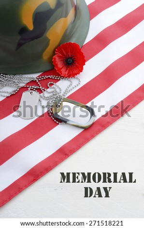 USA Memorial Day concept with dog tags and red remembrance poppy on American stars and stripes flag on white vintage wood table with title text.  - stock photo