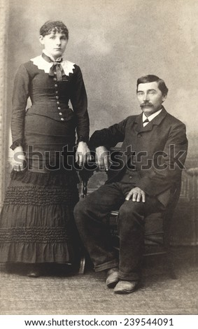 USA MICHIGAN CIRCA 1885  A Vintage Carte De Visite photo of a couple. He is sitting in a chair and she is standing. Photo from the Victorian era. CIRCA 1885 - stock photo