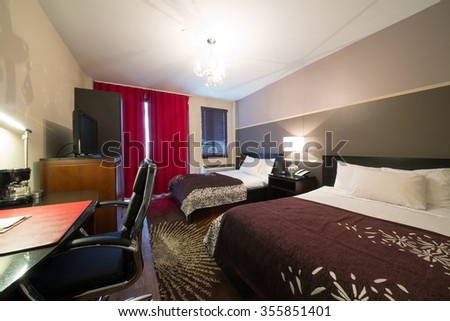 USA, NEW-YORK - 24 AUG, 2014: Room with two double bed, TV and red draperies in Hotel Vetiver, Queens.