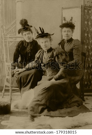 USA - NEW YORK - CIRCA 1895 A vintage cabinet card photo of three women. They are sitting and wearing Victorian style clothing with fancy hats and feathers. Photo is from the Victorian era. CIRCA 1895 - stock photo