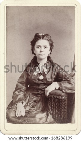 USA - NEW YORK - CIRCA 1860 - A vintage Cartes de visite photo of a young woman dressed in a Victorian style hoop skirt dress. She is sitting in a chair. A photo from the Civil War era. CIRCA 1860 - stock photo