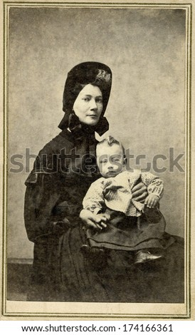 USA - NEW YORK - CIRCA 1865 - A vintage Cartes de visite photo of young woman sitting in chair holding her baby. She is dressed in hoop skirt dress.  Photo from the Civil War Victorian era. CIRCA 1865 - stock photo