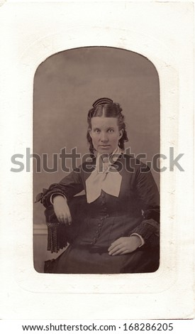 USA - NEW YORK - CIRCA 1860 - A vintage tintype photo of an young woman dressed in a Victorian style. She has a fancy hair pin.  She is sitting in a chair. A photo from the Civil War era. CIRCA 1860 - stock photo
