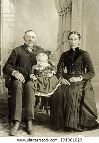 USA - NORTH DAKOTA - CIRCA 1895 A vintage photo of a Victorian family. The parents or grandparents are older with a small child. The man has a mustache. Photo is from the Victorian era. CIRCA 1895 - stock photo