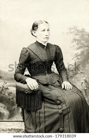 USA - PENNSYLVANIA - CIRCA 1890 A vintage cabinet card photo of a young woman sitting in  chair. She is dressed in a Victorian style dress. Photo is from the Victorian era. CIRCA 1890 - stock photo