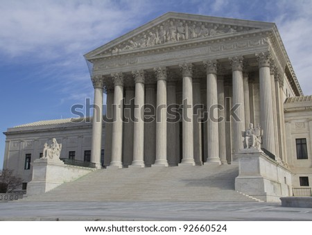 USA Supreme Court building in Washington, D.C. with a cloudy blue sky background.