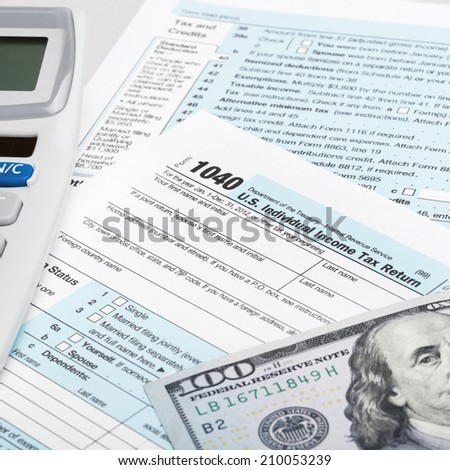 USA Tax Form 1040 with calculator and 100 US dollar bills - stock photo