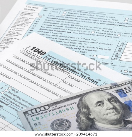 USA Tax Form 1040 with calculator and 100 US dollar bills - 1 to 1 ratio - stock photo